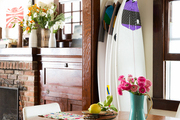 A collection of surf boards near a wooden dining table