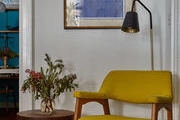 This canary yellow chair brightens up a corner seating area.