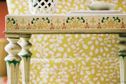 A painted side table and a yellow patterned armchair atop a white rug