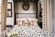 A patterned settee at the foot of a canopy bed