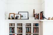 A white bookcase with a Moroccan pouf.