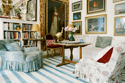 Floral skirted armchairs and a striped rug in a living space filled with art