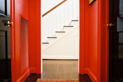 A hallway with black doors, red walls, and a patterned rug