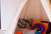 A tepee strewn with pillows and plush toys at Thomas Sires