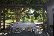 Wood and plant canopy over white outdoor dining table.