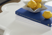 A sculptural coffee table is topped with books and sculptural dish of lemons.