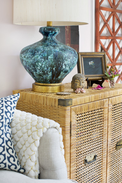 Tami Ramsay - A table lamp atop a rattan cabinet in a living room
