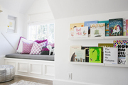 Built-in bookshelves and a built-in window seat in a sunny kids bedroom