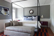 A four-poster bed on an offset-stripe rug