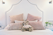 A girl's bedroom with a pink-and-white palette