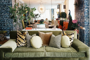 A green velvet midcentury sofa with tiger-print pillows