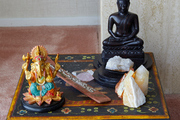A small side table with various crystals and a buddha sitting on top.