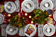 A colorful table setting with silver plates and colorful flower arrangements.