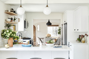 An all white kitchen with hanging globe lights and black and white geometric tile.