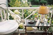 A patio chair and a side table with a lamp on a porch