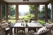 A wooden dining table surrounded by rattan chairs in a screened-in porch