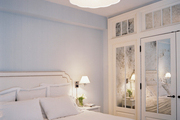 A scalloped light fixture paired with mirrored closets and a white bed and bedding