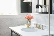 A contemporary bathroom with white marble and black accents.