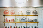 Patterned dishes and mugs on brass shelves