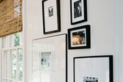 A grouping of framed art on white walls