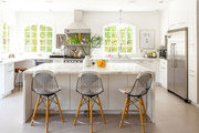 A trio of wire chairs at a Calacatta Gold marble kitchen island
