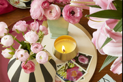 Vibrant pink floral arrangements sitting on top of wooden dining table.