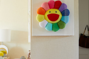 A playful cushion is framed on a wall.
