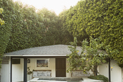 Lush trees surround a pool house and swimming pool