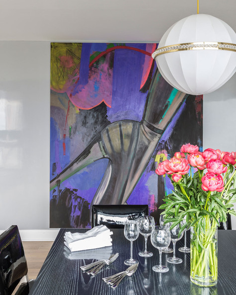Urban - A large painting and white pendant lamp near a black dining table with patent leather chairs