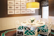 White fretwork chairs with green cushions in a dining nook with grass-cloth wallpaper