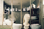 A grouping of bowls, platters, and a bust on a set of shelves