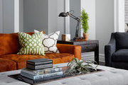 Small stack of books atop padded bench in modern living room.