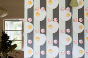 A detail of striped wallpaper with eggs on it.
