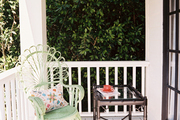 A green wicker chair and a faux-bamboo side table on a porch