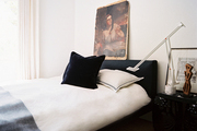 An upholstered bed with white bedding and a modern task lamp