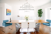A dining room with multi color chairs, a wooden table top, and steel legs.