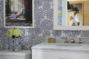Patterned wallpaper and white cabinetry in vibrant bathroom.