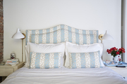 Patterned headboard and pillows atop white bedding.