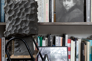 An artful bookshelf with objects and artwork on it.