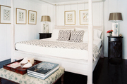 A white canopy bed and an ottoman topped with a tray in a bedroom