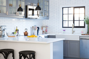 Matching black stools under white kitchen island in white brick kitchen.
