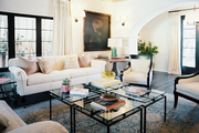 A white sofa and pair of chairs with a grouping of four glass end tables