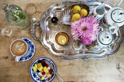 A tray holding flowers, a bowl of lemons, and coffee-service needs