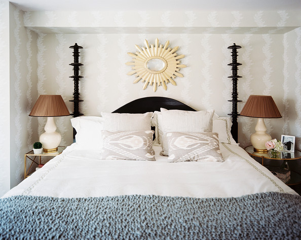 Wallpaper  - A black four-poster bed dressed with neutral linens and a gray-blue throw