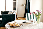 A breakfast table with striped chairs and flowers at Palihouse Santa Monica