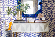 A blue and white entry way features a modern white console table, a blue mirror, and a blue and white umbrella stand to match.