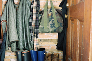 Boots lining an entryway with hooks for coats