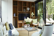 Large built in shelving behind White furniture on seagrass area rug.