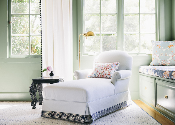 Window Seat - A white chaise longue trimmed with a Greek key pattern in a bedroom with floral accents