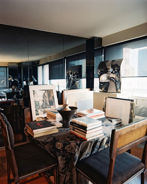 Work Space - A dining table topped with books and pieces of art